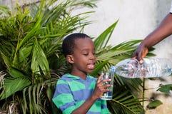 Используемый ребенок, вода, стекло, отец, усмехаясь, семья, счастливый, усмехаясь, мальчик, малый, бутылка, удерживание, цветок,  стоковые изображения