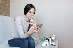 Используйте nebulizer и ингалятор для обработки Молодая женщина вдыхая через маску ингалятора и смотря телефон Взгляд со стороны стоковое изображение