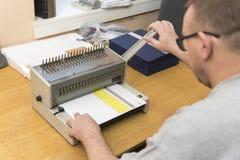 Используя бумажную binding машину стоковая фотография rf
