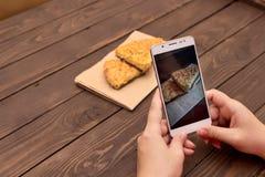 Используя мобильный телефон для того чтобы сфотографировать еду Фото еды для рекламировать или социальные средств массовой информ стоковые изображения rf