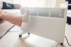 Используя подогреватель дома в зиме Женщина грея ее ноги Сезон топления стоковое фото