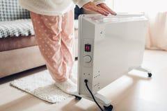 Используя подогреватель дома в зиме Женщина грея ее руки Сезон топления стоковые изображения