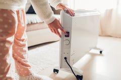 Используя подогреватель дома в зиме Подогреватель женщины поворачивая дальше Сезон топления стоковые фотографии rf