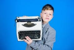 Используя ретро технологию Мальчик держа ретро машинку на голубой предпосылке Небольшой мальчик имея старую машинку франтовск стоковое изображение