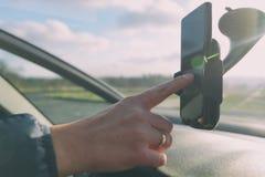 Используя телефон пока управляющ автомобилем стоковая фотография