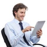 Исполнительная власть сидя на стуле просматривая таблетку стоковое изображение