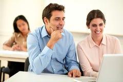 Исполнительные пары работая и смотря на компьтер-книжке Стоковые Изображения RF
