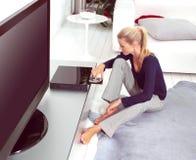 Использование женщины DVD-плеер в квартире Стоковые Фотографии RF