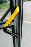 Используемая ручка двери от желтого цвета черноты кабины телефона стоковая фотография