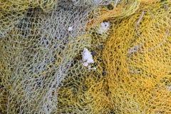 Используемая рыболовная сеть лежа на поле стоковые фотографии rf