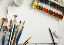 Используемые краск-коробка вод-цвета, бумага акварели и кисть стоковое изображение