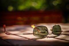 Используемые солнечные очки на деревянном столе. Стоковая Фотография RF