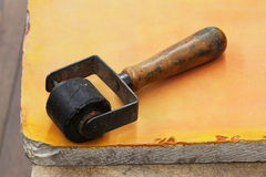 Используемый винтажный резиновый ролик для letterpress, оранжевой каменной предпосылки Инструменты Diy, концепция аксессуаров офо Стоковое Изображение RF