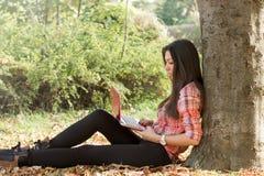 Используя компьтер-книжка-студента учит outdoors Стоковое Фото