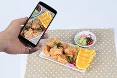 Используя мобильный телефон для того чтобы принять фото блюдо зажаренных наггетов тофу для доли к социальной сети Селективный фок Стоковое фото RF