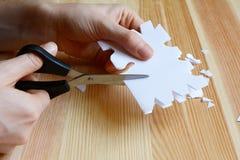 Используя ножницы для того чтобы отрезать вне бумажную снежинку сформируйте Стоковое фото RF