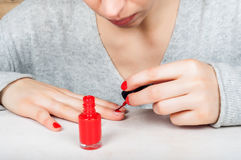Используя щетку аппликатора для того чтобы приложить заполированность красного цвета к ногтю, собственная личность m стоковые изображения