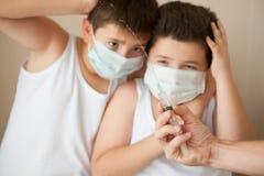 2 испуганных мальчика в медицинской маске смотря под рукой с шприцем Стоковые Фотографии RF