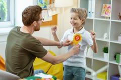 Испуская лучи активный ребенк в белой футболке имея яркий награждая знак стоковые фотографии rf