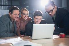 Испуская лучи коллеги наблюдая на компьютер-книжке Стоковое фото RF