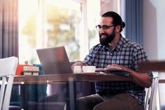 Испуская лучи приятный зрелый человек читая важные документы на ноутбуке стоковая фотография rf
