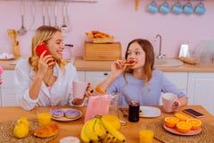 Испуская лучи старшая сестра наблюдая, как ее милая девушка съела тосты с вареньем стоковое изображение