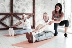 Испуская лучи старшая тренировка женщины и человека на фитнес-клубе Стоковые Фото