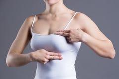 Испытание груди, женщина рассматривая ее груди для рака, сердечного приступа, боли в человеческом теле стоковая фотография rf