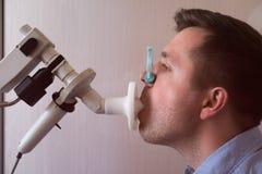 Испытание молодого человека дышая функцией спирометрией стоковое фото