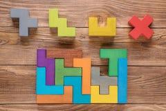 Испытание IQ выбирает правильный ответ Логически задачи составленные красочных деревянных форм Задача ` s детей воспитательная ло Стоковое Фото