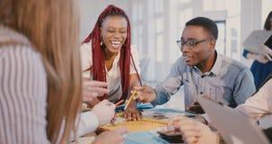 Испытанная молодая Афро-американская женщина руководителя финансовой компании работает вместе с многонациональными работниками на видеоматериал