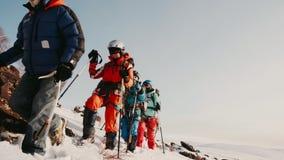 Испытанный альпинист и его вышколенная команда на снежных боеприпасах горных склонов полностью Он проверки особенного крюка акции видеоматериалы