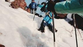 Испытанный альпинист стоит вверху наклон и наблюдать горы как его попытки команды преодолевать трудный подъем видеоматериал