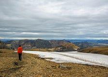 Испытанный мужской hiker самостоятельно в дикий восхищаясь вулканический ландшафт с красочными горами и снегом с большой, тяжелый стоковое изображение rf