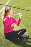 Испытывающая жажду молодая красивая питьевая вода девушки фитнеса белокурых волос на стадионе Деятельность при спорта лета Зелена стоковые изображения