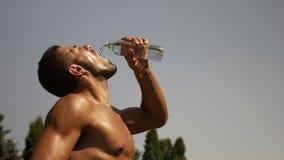 Испытывающий жажду атлетический человек льет воду в его рте после бежать сток-видео