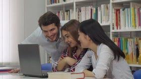 Исследование 2 девушек на компьтер-книжке на библиотеке стоковое изображение rf
