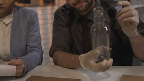 Исследователь принимая отпечатки пальцев от бутылки доказательства работая женский коллега акции видеоматериалы