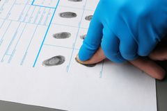 Исследователь принимая отпечатки пальцев подозреваемого на таблицу Уголовная экспертиза стоковое изображение