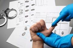 Исследователь принимая отпечатки пальцев подозреваемого на таблицу Уголовная экспертиза стоковые фотографии rf