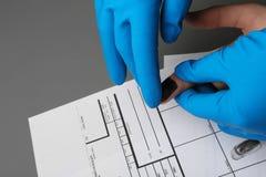 Исследователь принимая отпечатки пальцев подозреваемого на таблицу Уголовная экспертиза стоковая фотография