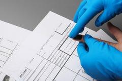Исследователь принимая отпечатки пальцев подозреваемого на таблицу Уголовная экспертиза стоковая фотография rf