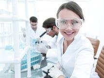 Исследователь проверяя пробирки, женщину носит защитные изумленные взгляды стоковое фото rf