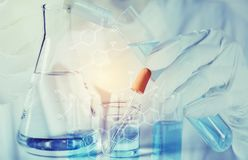 Исследователь с пробирками стеклянной лаборатории химическими с жидкостью для аналитического, медицинской, фармацевтического и на стоковое изображение rf