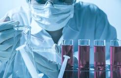 Исследователь с пробирками стеклянной лаборатории химическими с жидкостью стоковое фото rf