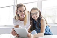 Исследовать школьницы онлайн с наведением ее учителя стоковое изображение