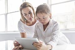 Исследовать школьницы онлайн с наведением ее учителя стоковая фотография