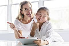 Исследовать школьницы онлайн с наведением ее учителя стоковые изображения