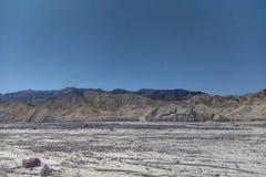 Иссушанное река в пустыне против фона гор стоковые фотографии rf