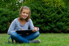Исследование девушки на таблетке в усмехаться сада счастливый Стоковые Фото